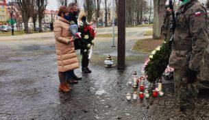 Zdjęcie przedstawia starostę gołdapskiego, wicestarostę i skarbnik powiatu, składających kwiaty i znicze pod Pomnikiem Niepodległości w Gołdapi.