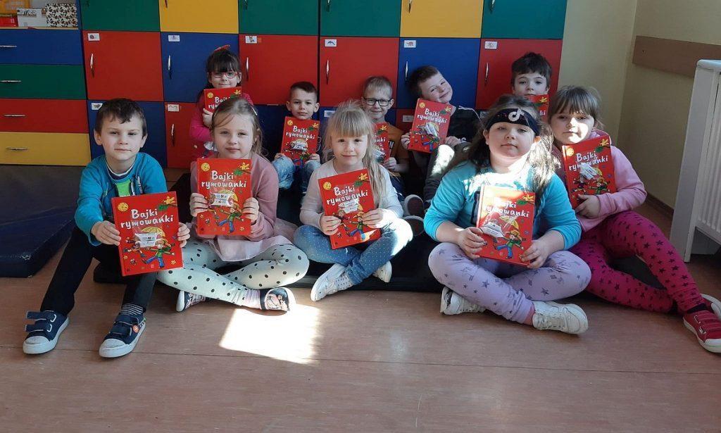 1.Grupa dzieci siedząca na materacach, na tle kolorowych szafek. Dzieci prezentują książkę o czerwonej okładce