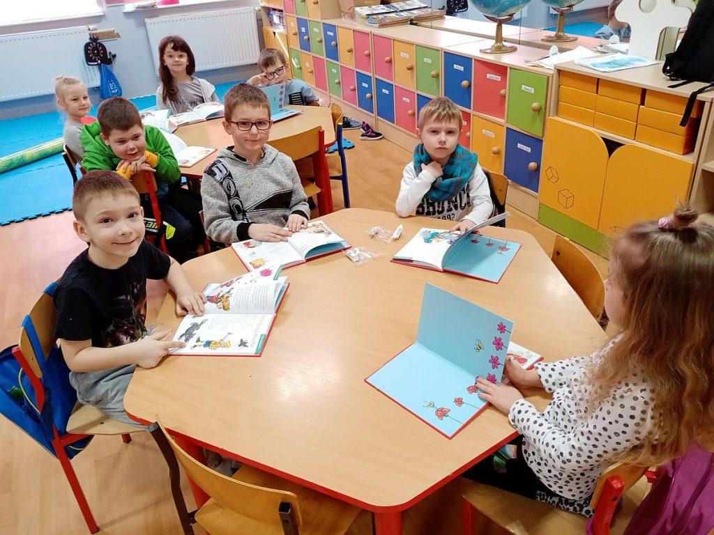 10.Grupa dzieci siedząca przy stolikach i czytająca książki