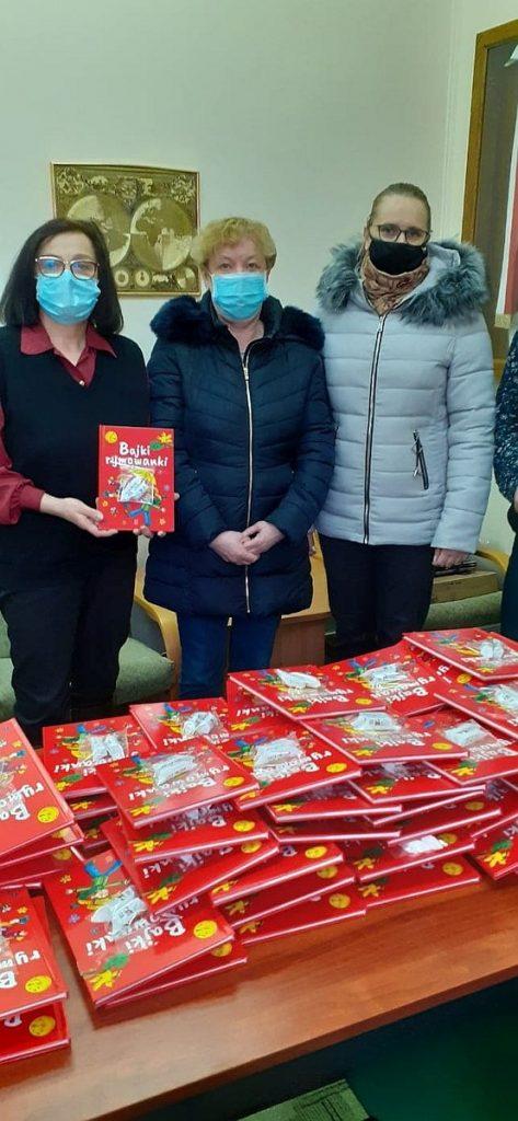 11.Pani dyrektor szkoły podstawowej numer 5 w Gołdapi prezentuje czerwoną książkę pod tytułem Bajki rymowanki, obok niej stoi bibliotekarka i dyrektor Biblioteki Publicznej w Gołdapi. Przed nimi na stoliku znajduje się dużo książek.