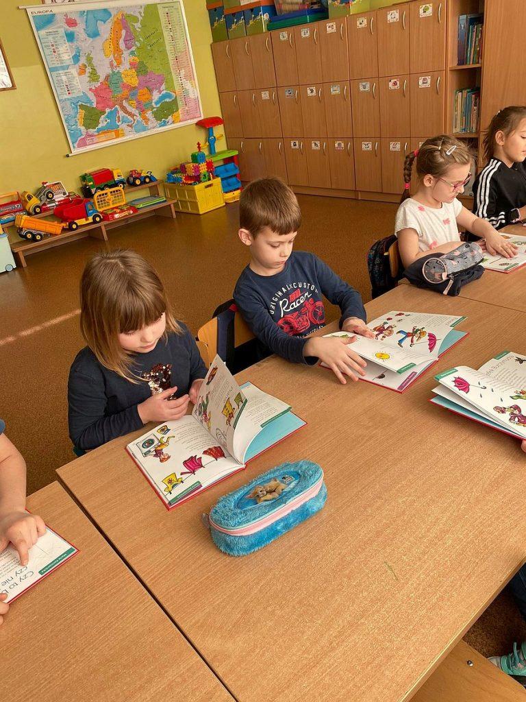 12.Dzieci siedzą przy stoliku i przeglądają książki