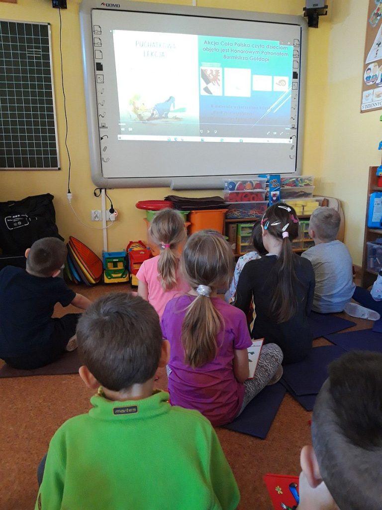 15.Grupa dzieci siedząca przodem do tablicy interaktywnej na której wyświetlony jest film