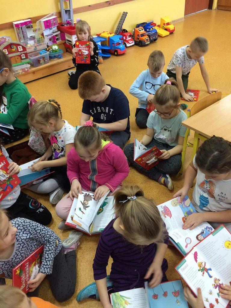 16.Grupa dzieci siedząca na podłodze. Wszystkie dzieci przeglądają książki