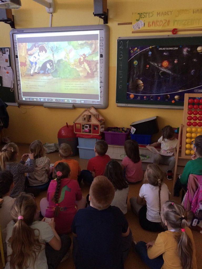 17.Grupa dzieci siedząca przodem do tablicy interaktywnej na której wyświetlony jest film