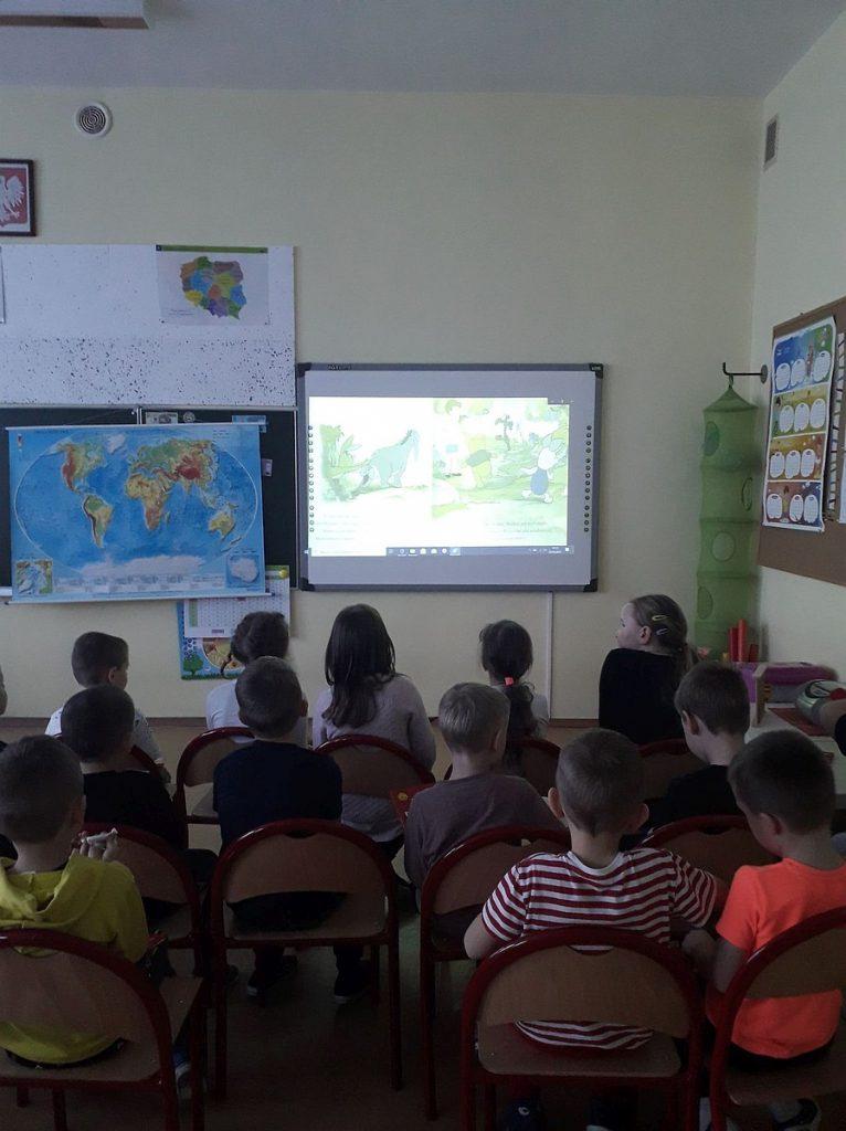 2.Grupa dzieci siedząca przodem do tablicy interaktywnej na której wyświetlony jest film.