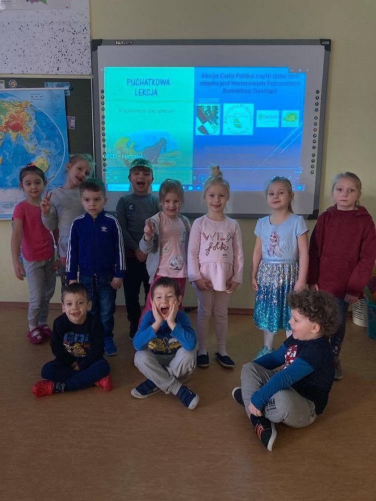 3.Grupa dzieci stojąca przy tablicy interaktywnej. Troje z nich siedzi  na podłodze