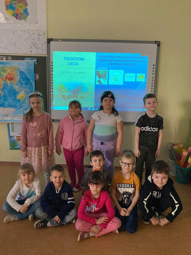 4.Grupa dzieci stojąca przy tablicy interaktywnej. Część z nich siedzi  na podłodze