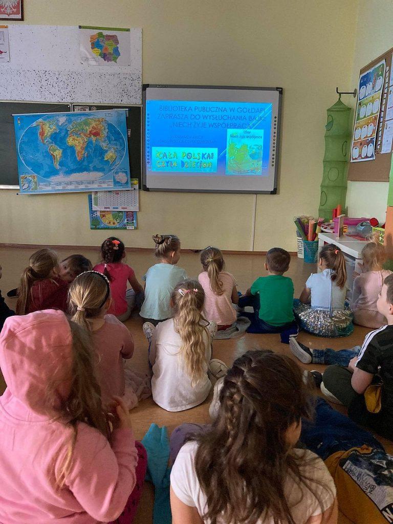5.Grupa dzieci siedząca przodem do tablicy interaktywnej na której wyświetlony jest film