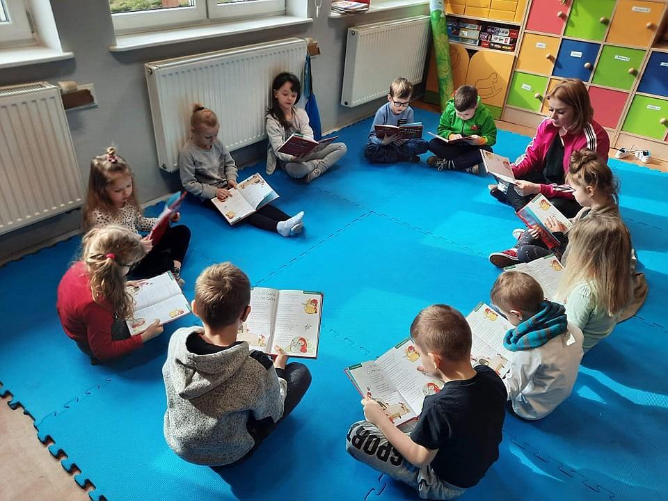 6.Grupa dzieci siedząca na niebieskim materacu z opiekunem. Wszyscy czytają książki