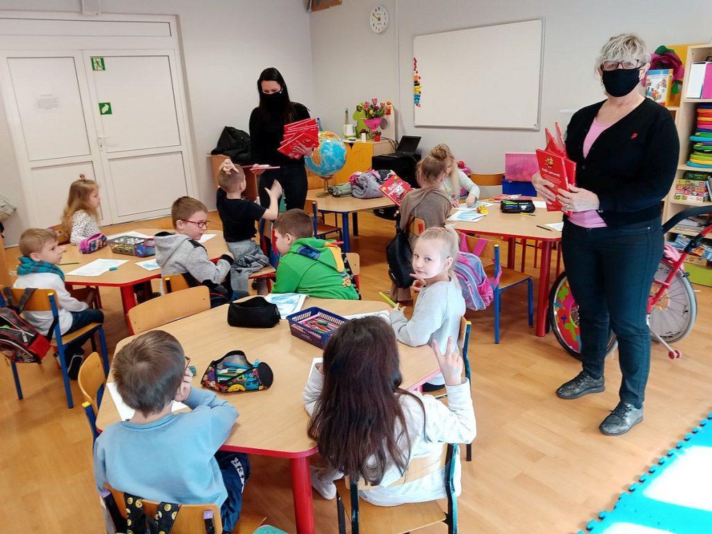 7.Grupa dzieci siedzi przy stolikach. Jedna z pań ubrana na czarno rozdaje dzieciom czerwone książki. Druga pani ubrana na ciemnio trzyma kilka czerwonych książek.