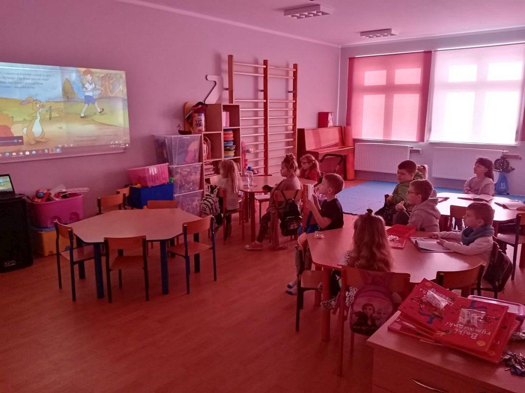 8.Grupa dzieci siedząca przy stolikach i oglądająca wyświetlany film na tablicy interaktywnej