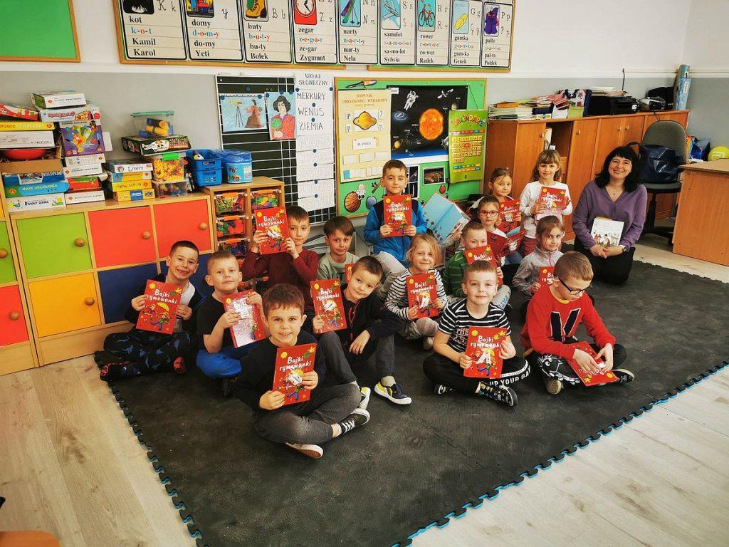 9.Grupa dzieci z opiekunem siedzące na czarnym dywanie, na tle kolorowych szafek. Dzieci prezentują książkę o czerwonej okładce