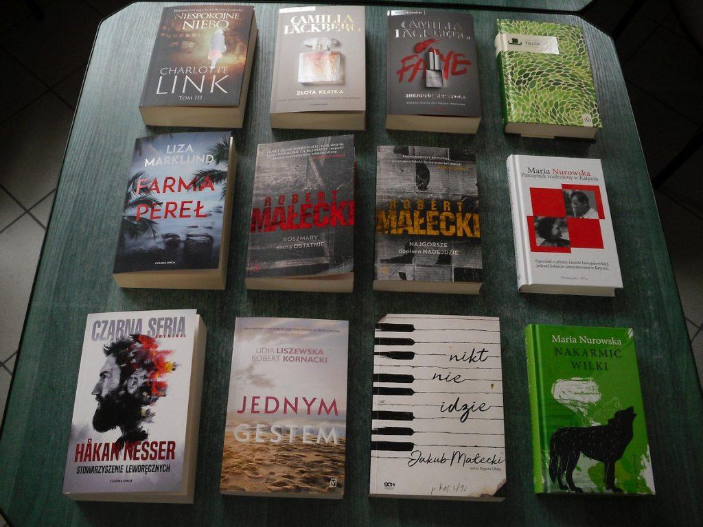 Na zielonym stole ułożono 12 książek w trzech rzędach. Wszystkie mają widoczne okładki.