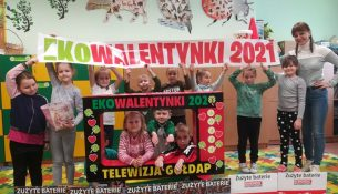 Zdjęcie przedstawia koordynatorkę akcji Ekowalentynki w raz z dziećmi, trzymającymi baner z hasłem akcji.