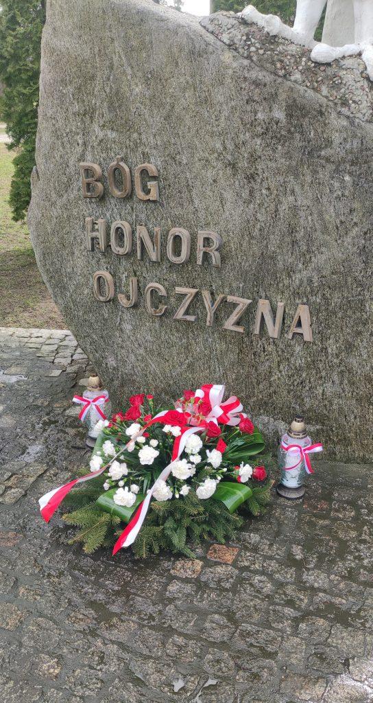 Kwiaty i znicz pod Pomnikiem Niepodległości w Gołdapi