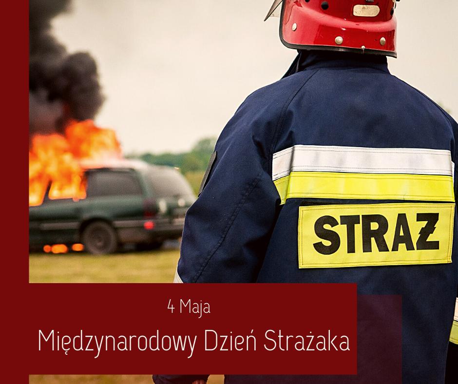 4 maja Międzynarodowy Dzień Strażaka - na zdjęciu widać strażaka, który stoi na tle palącego się samochodu