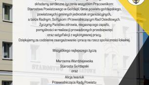 Życzenia na tle budynku Starostwa Powiatowego w Gołdapi, o treści: Z okazji Dnia Samorządu Terytorialnego składamy serdeczne życzenia wszystkim Pracownikom: Starostwa Powiatowego w Gołdapi, Gmin powiatu gołdapskiego, powiatowych i gminnych jednostek organizacyjnych, a także Radnym, Sołtysom i Przewodniczącym Rad Osiedlowych. Życzymy Państwu zdrowia, niegasnącego zapału, pomyślności w realizacji prowadzonych przedsięwzięć oraz satysfakcji z wykonywanej pracy. Dziękujemy za codzienne zaangażowanie i pracę na rzecz społeczności lokalnej. Wszystkiego najlepszego! Marzanna Wardziejewska Starosta Gołdapski Alicja Iwaniuk Przewodnicząca Rady Powiatu w Gołdapi