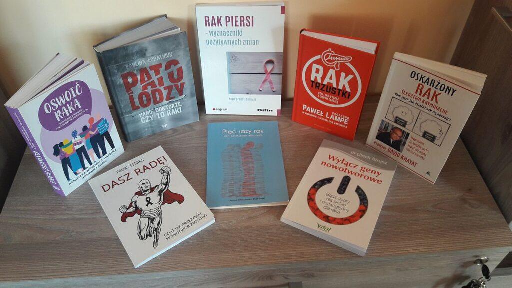 Osiem książek na temat raka (choroba) ułożonych na komodzie.