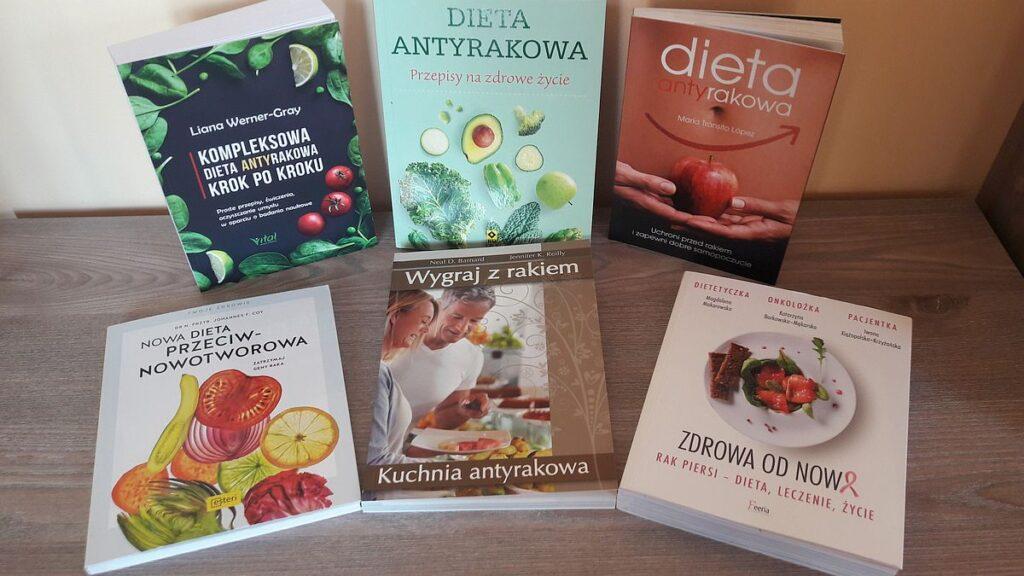 Sześć książek na temat diety antyrakowej ułożonych na komodzie.
