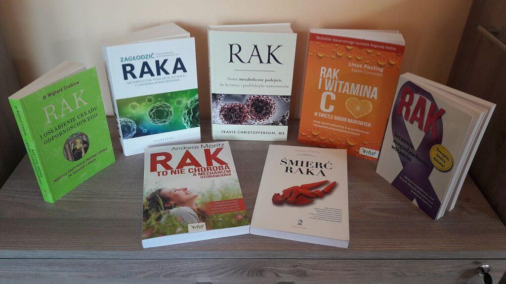 Siedem książek na temat raka ułożonych na komodzie.
