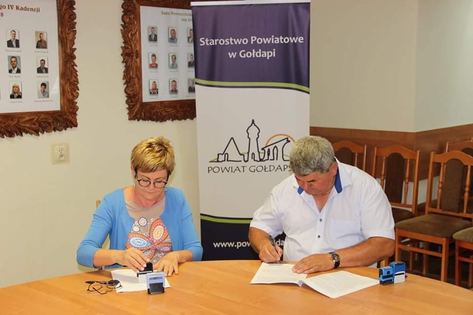 Starosta Gołdapski oraz prezes Przedsiębiorstwa Gospodarki Komunalnej Sp. z o.o siedzą przy stole i podpisują umowę.