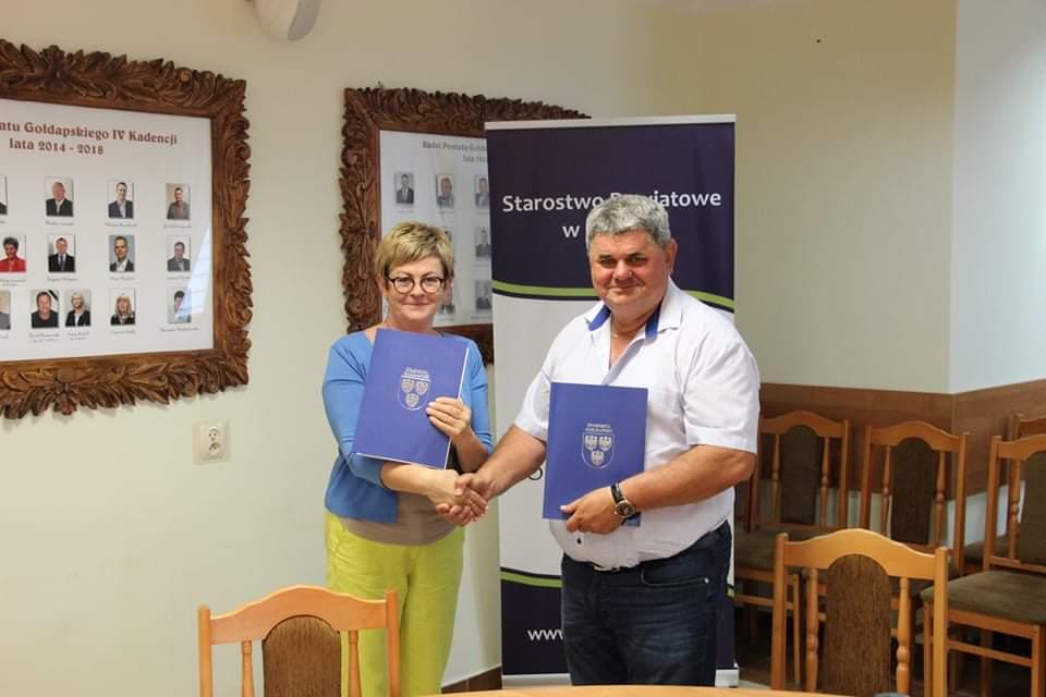 Starosta Gołdapski oraz prezes Przedsiębiorstwa Gospodarki Komunalnej Sp. z o.o siedzą podają sobie dłonie i wymieniają się egzemplarzami podpisanej umowy.