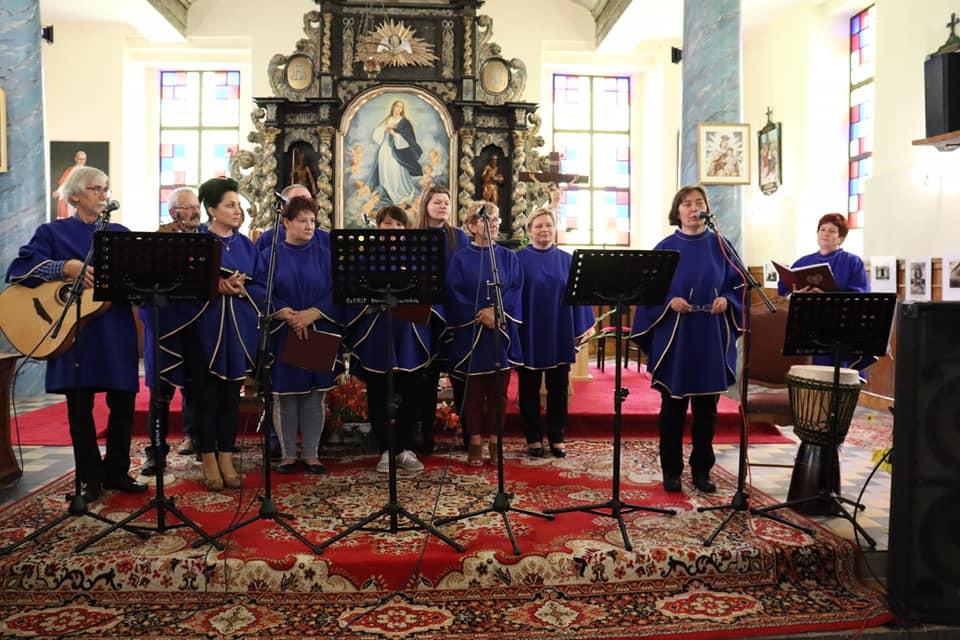 Jeden z zespołów uczestniczących w przeglądzie piosenki, kobiety i mężczyźni w niebieskich strojach z instrumentami muzycznymi na tle ołtarza.