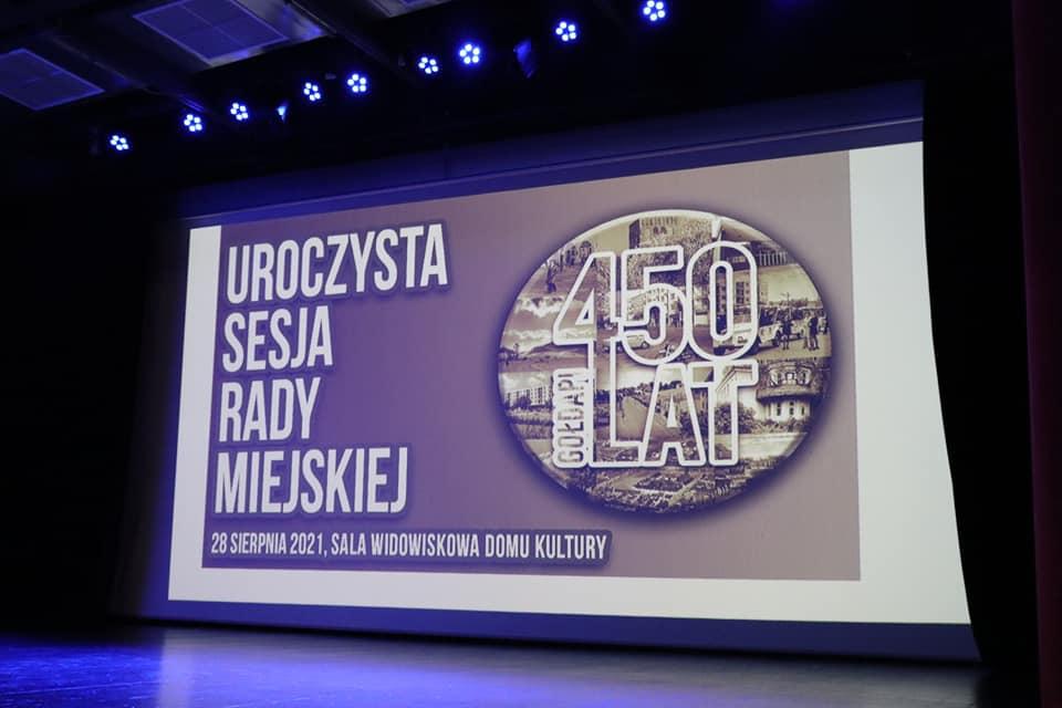Scena w domu Kultury w Gołdapi, napis na ekranie: Uroczysta Sesja Rady Miejskiej 28 sierpnia 2021
