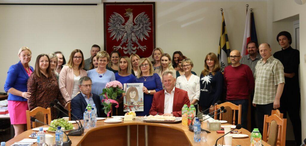 Zdjęcie grupowe pracowników Starostwa Powiatowego w Gołdapi podczas uroczystości pożegnalnej odchodzącej na emeryturę pani Łesi Predko.