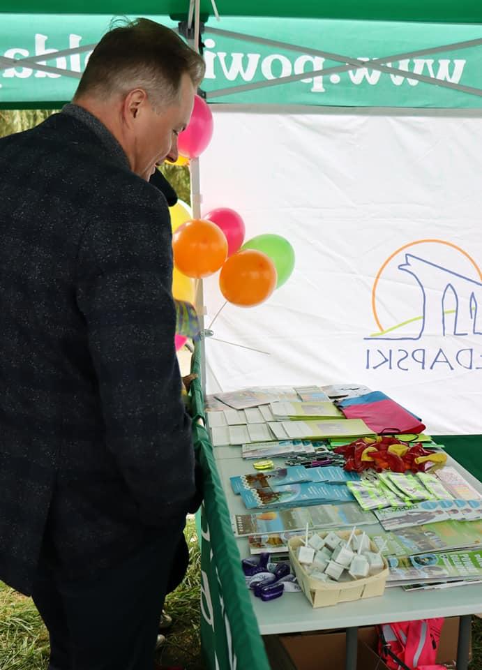 Wicemarszałek Województwa Warmińsko - Mazurskiego w środku namiotu ogląda materiały promocyjne powiatu.