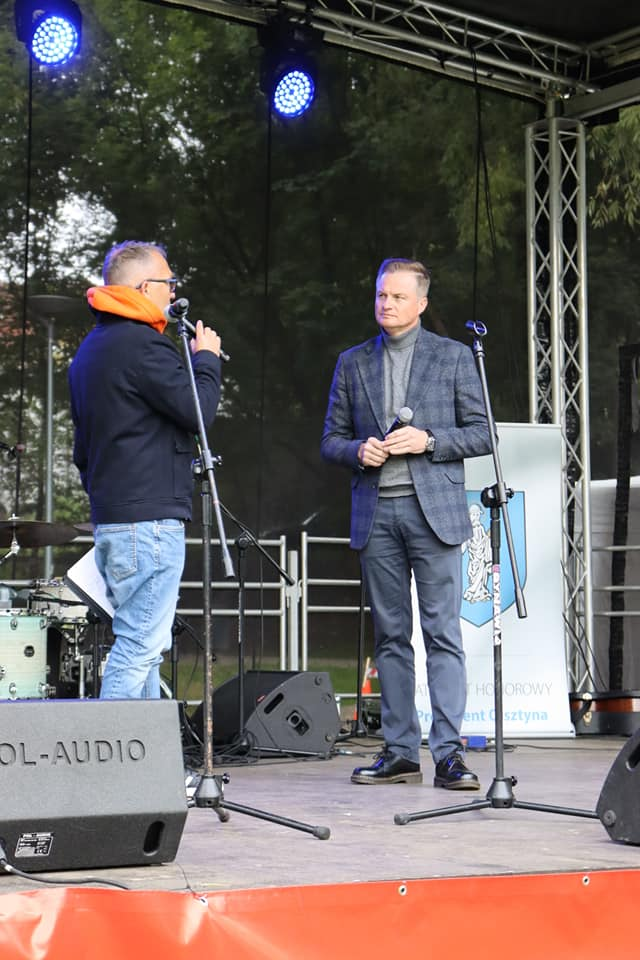 Oficjalne rozpoczęcie pikniku Love rower, scena i dwóch mężczyzn: wicemarszałek województwa warmińsko-mazurskiego i prowadzący wydarzenie.
