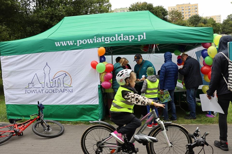 Namiot promocyjny powiatu gołdapskiego, w środku uczestnicy pikniku rowerowego.