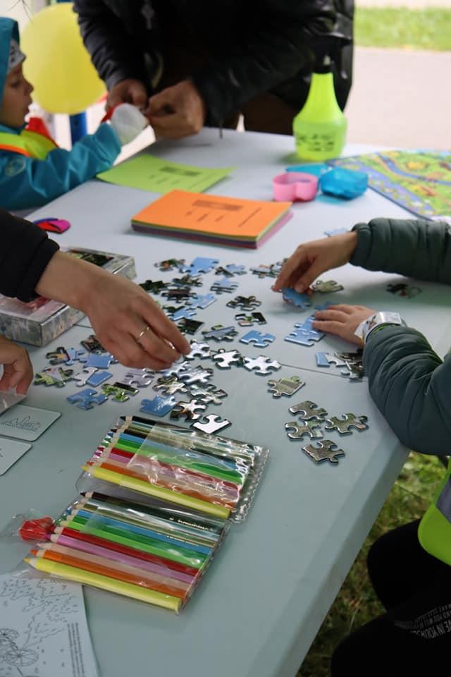 Dzieci układają kolorowe puzzle przy stoliku.