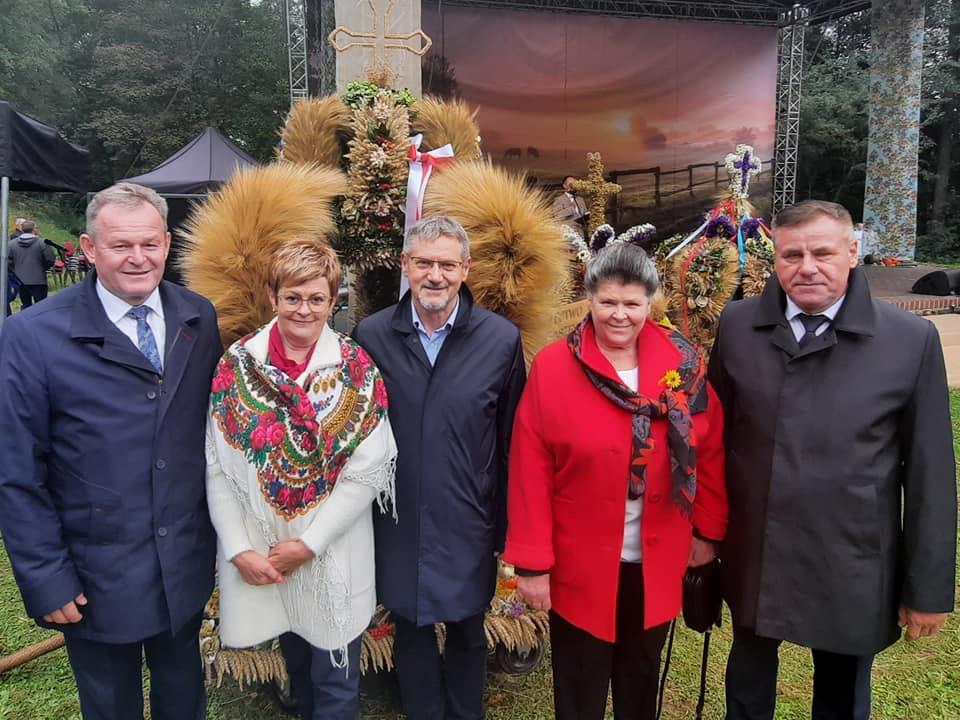 Delegacja powiatu gołdapskiego na dożynkach. W tle wieniec dożynkowy i  scena.