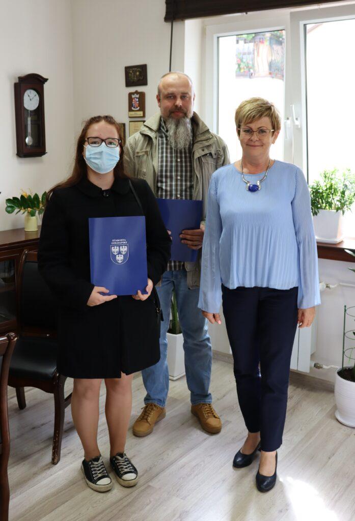 Zdjęcie grupowe w gabinecie ze starostą gołdapskim wyróżnioną uczennicą i jej ojcem.