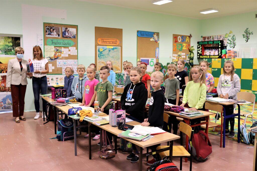 Zdjęcie grupowe zrobione w klasie, na zdjęciu dzieci wraz z opiekunką i starosta gołdapskim.