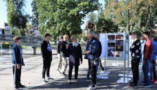 Starosta gołdapski oglada wystawę w toawarzystwie młodzieży i ich opiekuna.