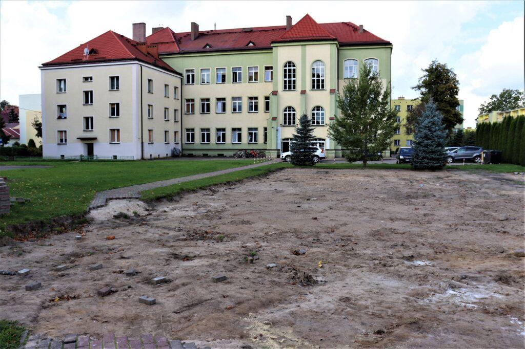 Zdjęcie przedstawia budowę boiska wielofunkcyjnego, chodnik, pas zieleni, rozkopane podłoże, w tle LO.