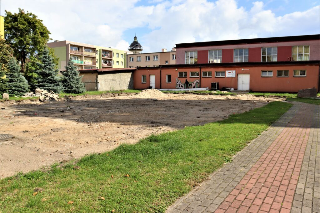 Zdjęcie przedstawia budowę boiska wielofunkcyjnego, chodnik, pas zieleni, rozkopane podłoże, w tle sala gimnastyczna.
