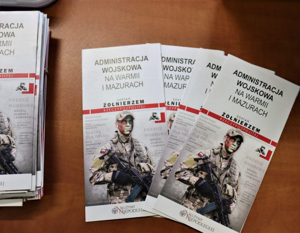 Na stole leżą ulotki z żołnierzem, zawierające informacje o kwalifikacji wojskowej.