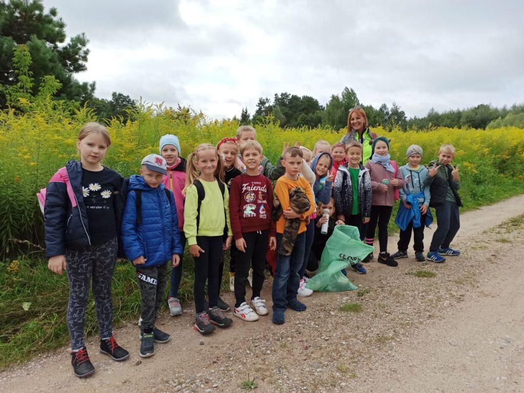 Grupa dzieci wraz z opiekunką, pozują na tle przyrody.