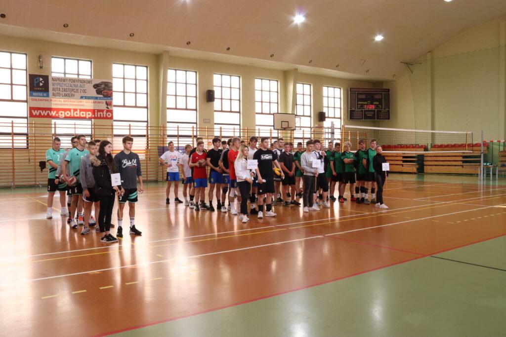 Zawodnicy stoją na płycie hali sportowej w podziale na drużyny, które reprezentują.